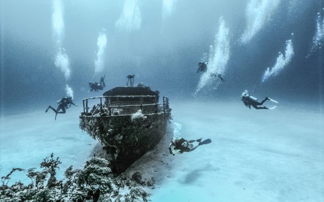 Divers Exploring a wreck underwater photographer Zac Macaulay
